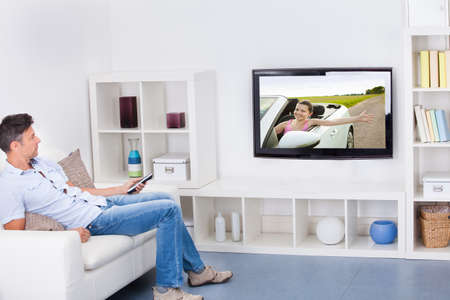 sofa television: Mature Man Sitting On Couch Watching Television