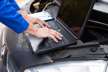 chassis: Close-up Of A Car Mechanic Using Laptop To Repair Car