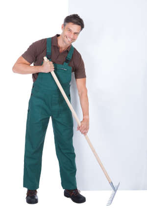 Male Gardener Working With Pitchfork In Front Of Blank Placard photo
