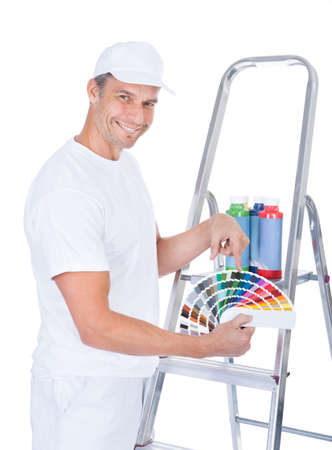 Mature Painter With Paint Bottles And Swatch Book photo