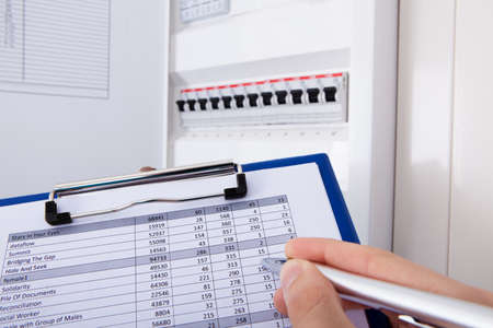 technical department: Close-up Of Hand Writing Machine Temperature Of Distribution Board On Form Stock Photo