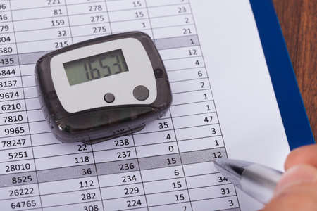 Close-up Of Hand Holding Pen Over Sheet With Digital Pedometer Stok Fotoğraf - 25151188