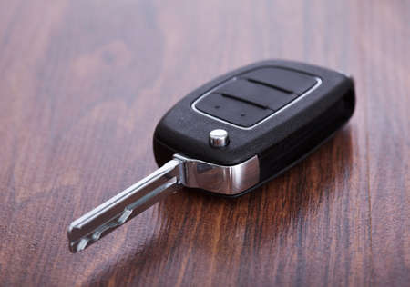 Close-up Of Black Car Key On Wooden Table photo