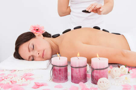 Person Placing Lastone On Woman's Back Lying On Massaging Table photo