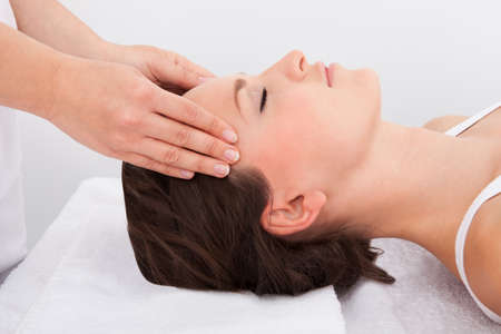 Young Woman With Eyes Closed Getting Massage Treatment From Masseuse Stock Photo - 25151259