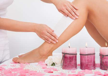 waxing: Beautician Waxing A Womans Leg Applying Wax Strip