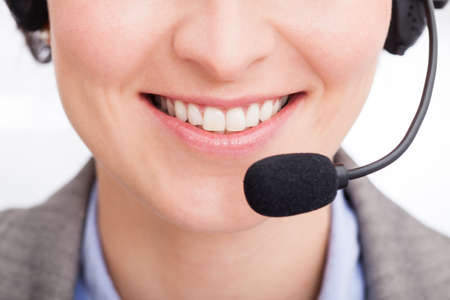 Close-up Of Happy Young Female Telephone Operator Talking On Headphones photo
