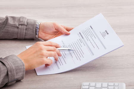 Close-up Of A Businesswoman At Desk Holding Resume photo