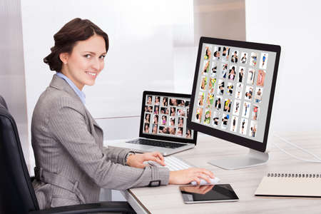 Portrait Of Happy Young Businesswoman Browsing Pictures On Computer photo