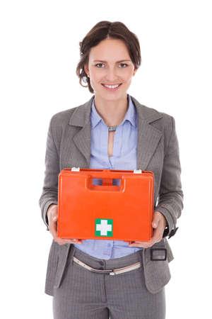 first aid box: Sonriente joven empresaria celebraci�n de Primera Caja de Ayuda Sobre Blanco
