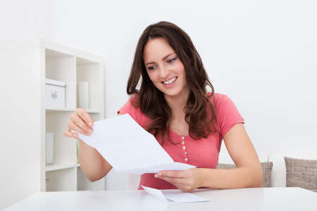 tax bills: Portrait Of A Smiling Young Woman Reading Documents Stock Photo