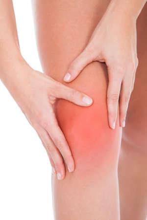 artrosis: Mujer joven que levanta lesiones en la pierna Aislado En Blanco Foto de archivo