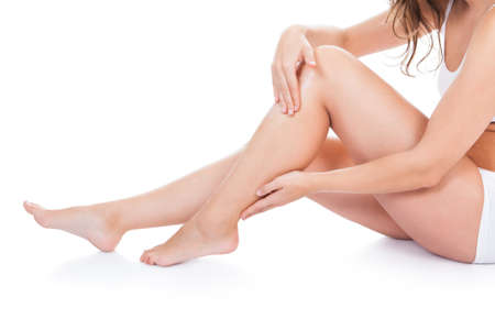 Close-up Of Young Woman With Beautiful Legs Sitting On White  photo