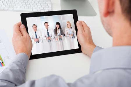 Close-up podnikatele při pohledu na video konference na digitální tablet Reklamní fotografie