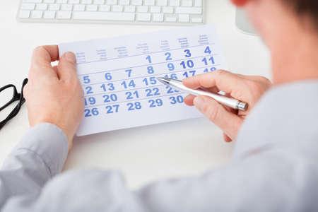 kalender: Close-up Of Man Kennzeichnung Mit Feder Und Auf Datum im Kalender