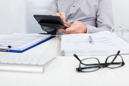 account executive: Close-up Of A Businessman Calculating Finance At Desk Stock Photo