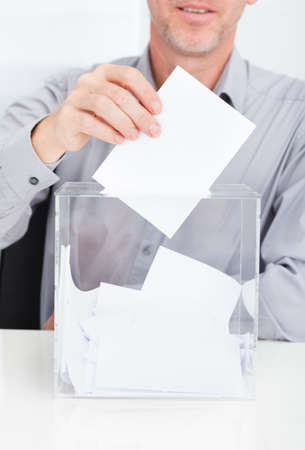 balloting: Close-up Of Person Inserting Ballot In Transparent Box