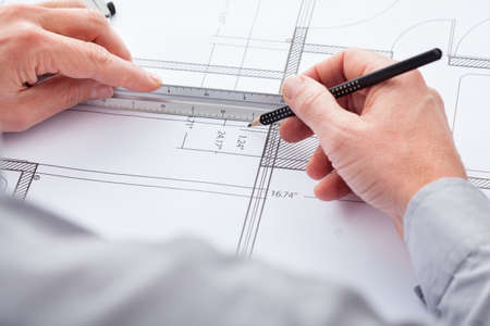 draftsman: Close-up Of Persons Hand Drawing Plan On Blue Print
