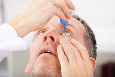 close eye: Close-up Of A Mature Man Putting Eye Drops In Eyes
