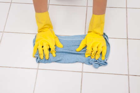 Close-up Of Young Maid Wearing Gloves Cleaning Floor photo