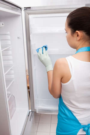 chores: Rear View Of A Young Woman Cleaning Refrigerator Stock Photo