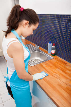 Portrait Of Young Woman Wearing Apron Cleaning Kitchen Worktop photo