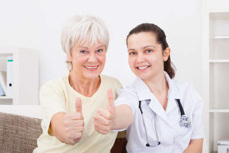 Happy Young Doctor And Senior Patient Showing Thumb Up Sign photo