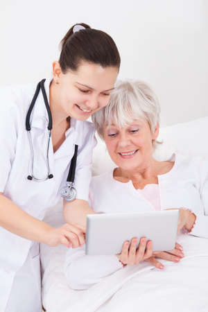 Young Female Doctor Showing Digital Tablet To Senior Female Patient photo