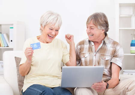Happy Senior Couple Shopping Online Using Laptop With Credit Card Stock Photo