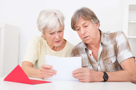 mail man: Senior Couple Were Disappointed While Reading Letter On Table Stock Photo
