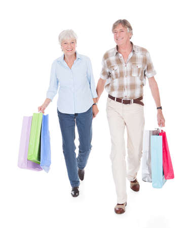 Happy Seniors Couple Walking With Shopping Bag Over White  photo