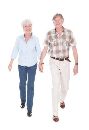 senioren wandelen: Gelukkig Hoger Paar Holding Hand En Lopen Over Wit Stockfoto