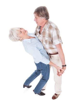 Portrait Of Happy Senior Couple Dancing Over White . photo
