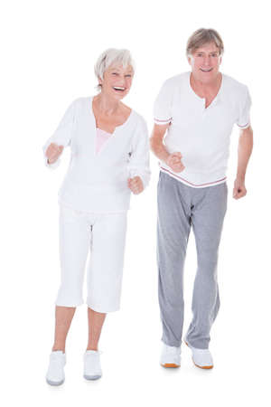 Portrait Of Happy Senior Couple Jogging On White  photo