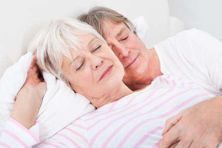 Portrait Of Loving Senior Couple Lying On Bed photo