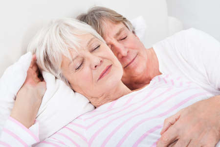 Portrait Of Loving Senior Couple Lying On Bed