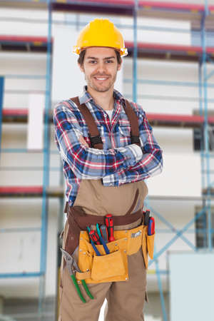 tradesman: Portrait Of Young Construction Worker With Tool Belt Stock Photo