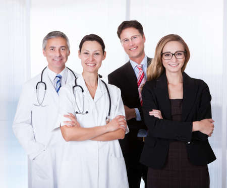 Portrait Of Confident Businesspeople And Medical Workers Standing Together photo