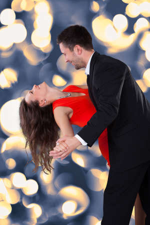 couple background: Portrait Of A Happy Couple Dancing On Black Background Stock Photo