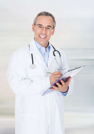 Portrait of a happy doctor writing on clipboard photo