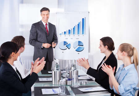applause: Group Of Happy Businesspeople Appreciating Businessman At Conference