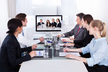 video conference: Businesspeople Sitting In A Conference Room Looking At Computer Screen