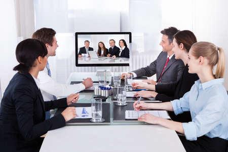 aziende: Imprenditori seduta in una sala conferenze guardando lo schermo del computer Archivio Fotografico
