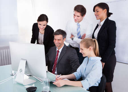 Portrait Of Happy Businesspeople In Office Looking At Computer photo