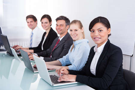 adult classroom: Happy Businesspeople In A Row Working Together At Office
