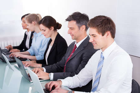 classroom training: Group Of Business Executives Sitting In A Row Stock Photo