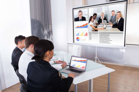 conference room meeting: Group Of Businesspeople In Video Conference At Business Meeting
