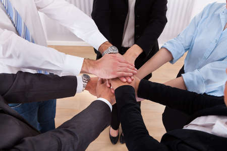 Close-up Of Businesspeople Putting Their Hands On Top Of Each Other photo