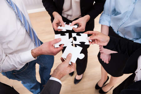 High Angle View Of Businesspeople Assembling Jigsaw Puzzle photo