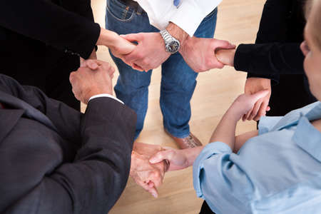 commitment: High Angle View Of Businesspeople Holding Hands